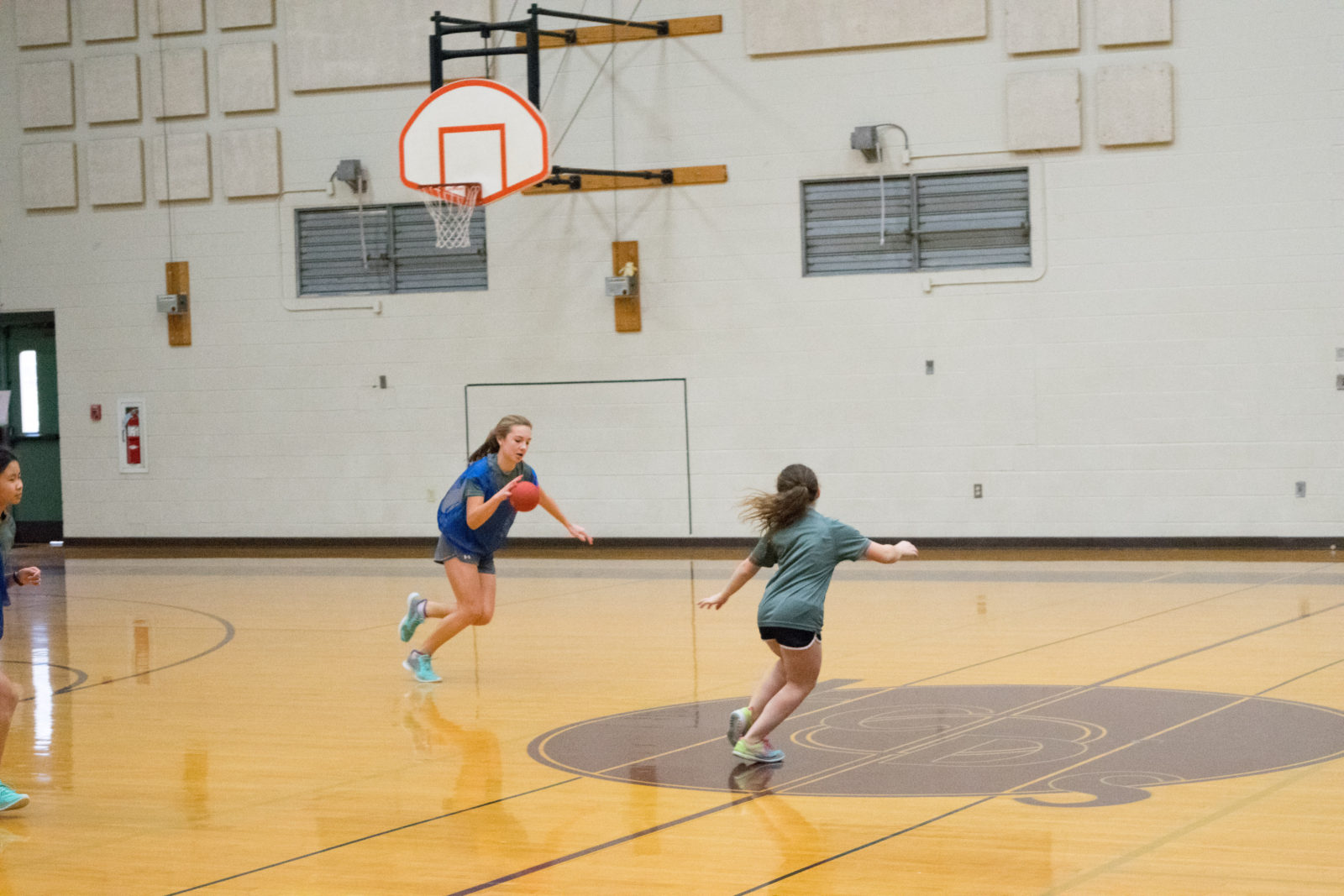 The seventh-grade girls gym class gets deep into a game of team handball.